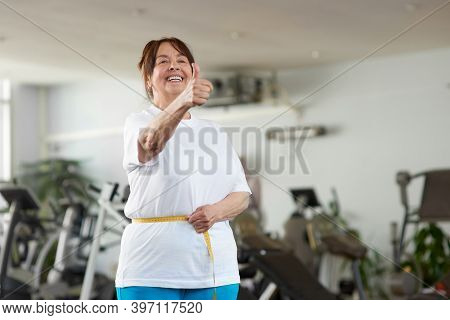 Senior Woman Measuring Her Waist At Gym. Mature Woman Expressing Success After Measuring Herself Wit