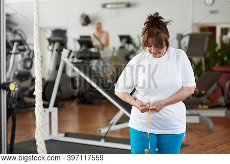 Mature Caucasian Woman Measuring Waist In Gym. Senior Lady Measuring Waist After Weightloss Diet And