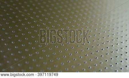 Industrial Toned Background In Olive Or Bronze Color. Perforated Metal Surface With Many Holes. Thei