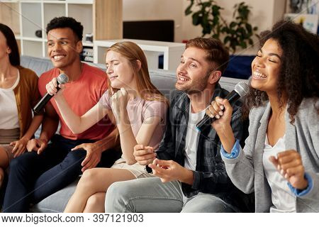 Singing Together. Joyful Friends Playing Karaoke At Home, Singing With Microphone While Sitting On T