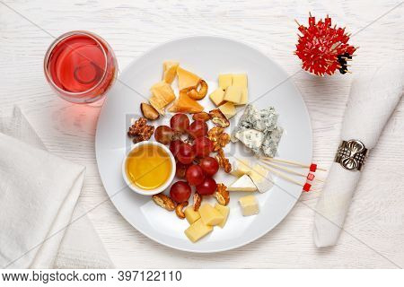 Cheese Plate Served With Grapes, Nuts And A Glass Of Rose Wine. Assorted Cheeses Camembert, Brie, Pa