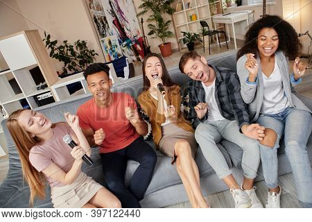 Karaoke Fans. Smiling Friends Looking Excited While Playing Karaoke At Home, Singing With Microphone