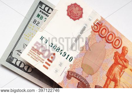 Russian Banknote Of 5000 Rubles And A Note Of 100 Dollars On A White Paper Background Close-up. Deva