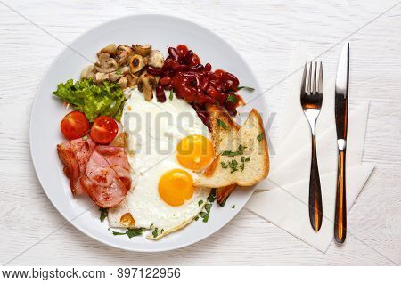 English Breakfast, Fried Eggs, Ham, Mushrooms On A White Plate With A Knife And Fork, On A White Woo