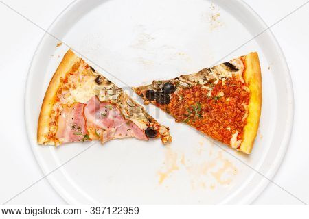 The Last Two Slices Of Pizza On A Large White Plate, Top View
