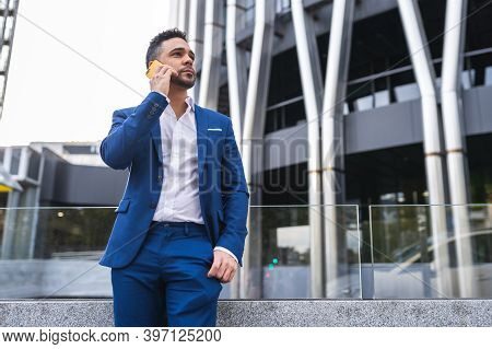 Businessman Having Phone Call Outdoors. Young Business Man Using Cellphone Outdoors. Business Concep