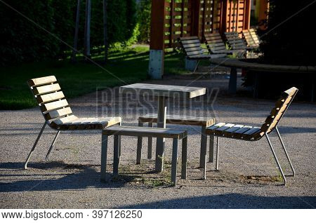 Park Furniture Chess Table And Chairs For Four Persons Made Of Light Metal And Wooden Beams With Bac
