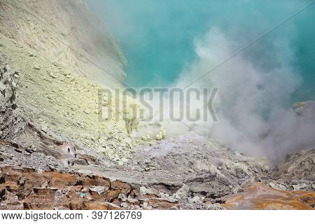 Volcano Ijen. Crater Of A Volcano With A Green Sulfuric Volcanic Lake And Volcanic Smoke. View Of Th