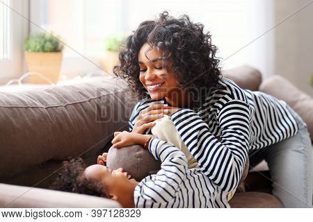 Happy Ethnic African American Family Mother With  Son Having Fun, Cuddle And Tickle While Lying On T