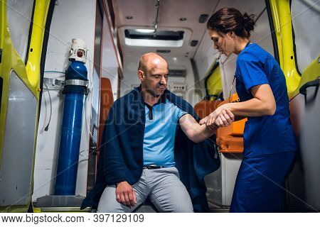 A Young Medical Worker Checking The Traumatized Hand Of Her Patient In An Ambulance Car.