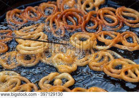 Frying Jalebi Batter In Oil. Red And Orange-colored Batter Will Be Dipped Into Sugar Syrup For A Swe