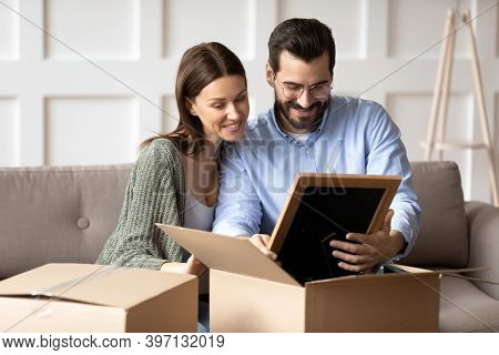 Happy Couple Renters Unpack Boxes Relocating To New Home