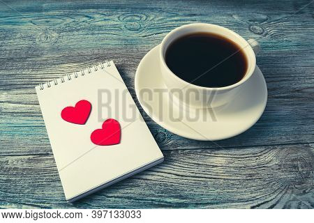 White Coffee Mug And Two Red Hearts On A Notepad On A Woodtwo Red Hearts On A White Notepad Next To