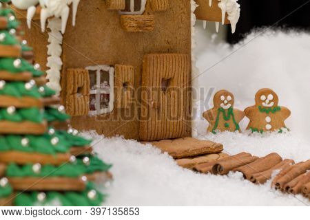 Cookie christmas tree and gingerbread house in a snow landscape