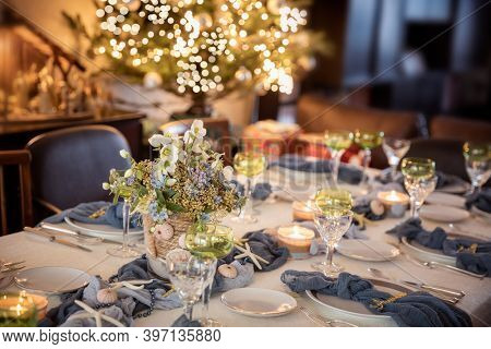 Christmas dinner table decorations in blues and gold following a beach theme with seashells and starfish
