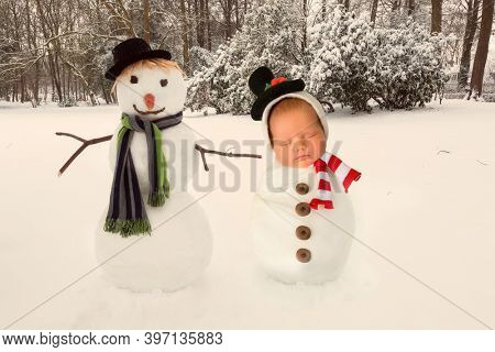 Sleeping newborn baby posing next to a real snowman
