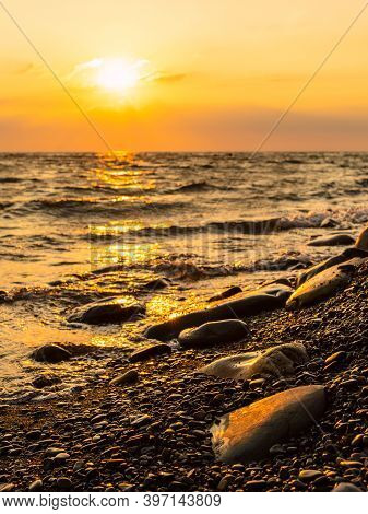 Sunset At The Sea. Vertical Frame. Pebble Beach And Surf At Sunset. Focusing On Tracing Pebbles In T