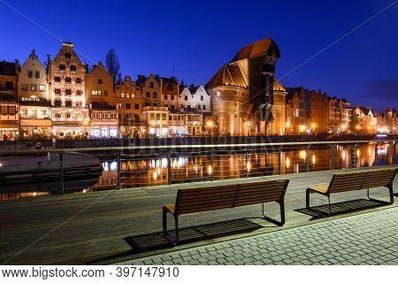 Promenade At Motlawa River With Famous Historic Port Crane At Night. Poland, Europe.