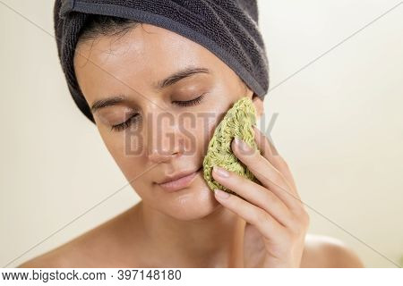 Young Woman Washing Her Face With Reusable Round Crocheted Pad In Bathroom. Diy Washable Knitted Mak