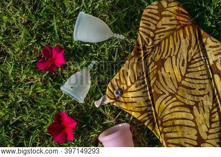 Reusable Female Hygiene Products On Grass. Top View Of Washable Menstrual Cups And Sanitary Napkin.