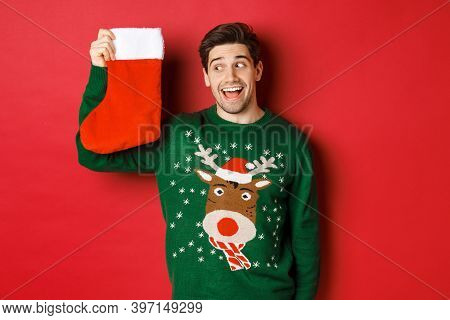 Image Of Surprised And Amused Man In Green Sweater, Looking At Christmas Stocking With Presents And