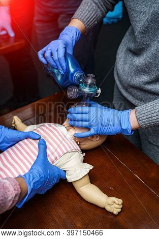 Cpr Training Medical Procedure. Demonstration Of Breast Compression On Cpr Baby Doll In Class.