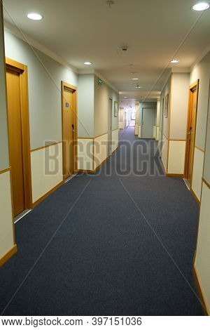 A View Of A Long Corridor In The Hotel, Lit By Daylight. Vacation Concept, Travel, Quarantine, Lockd