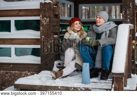 Walking Through The Woods In Winter A Man And A Woman Found A House And Sat On The Porch To Drink Co