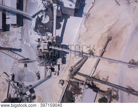 Large Quarry Stone Sorting Conveyor Belts And An Open Pit Mine. Industrial Building.