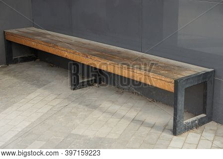 One Brown Wooden Bench Stands On The Sidewalk Near The Gray Metal Wall Of The Bus Stop