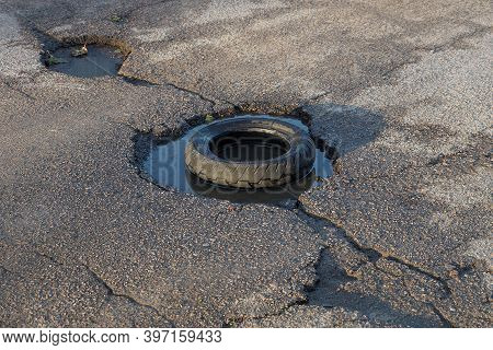 A Black Car Tire Lies In A Pothole With Water On A Gray Asphalt Road With A Crack