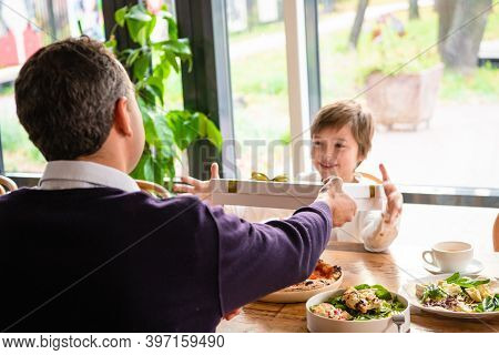 Family Of Two Having A Celebration, Father Giving A Present To His Son In A Cafe.