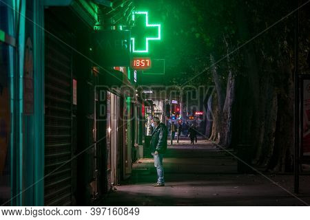 Belgrade, Serbia - November 15, 2020: Man Standing And Waiting At Night In Front Of A Pharmacy Weari