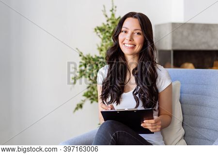 Portrait Of A Young Woman In The Office. Woman Writes Data To The Questionnaire