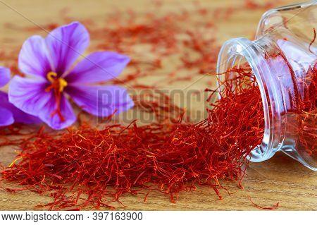 Saffron Stigmas Scattered On A Wooden Surface From A Glass Bottle. Saffron Crocus Flowers.