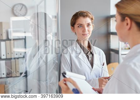 Waist Up Portrait Of Two Female Scientists Writing On Glass Wall And Holding Clipboard While Doing R