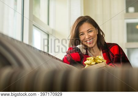 Asian Woman Holding A Gift Sitting On The Sofa.