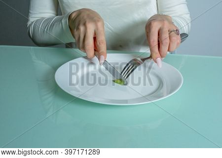 Woman With Anorexia Cuts A Small Portion Of Food.