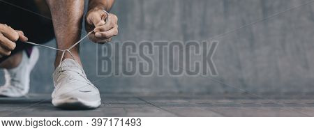 Male Athlete Tying Shoelaces Getting Ready For Exercise, Banner Background With Copy Space
