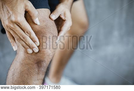 Young Man With Knee Pain, Hand Massaging His Painful Knee. Health Care And Medical Concept.