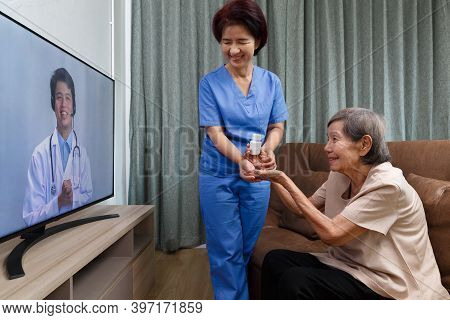 Elderly Woman Sit At Home Having Online Consultation With Doctor