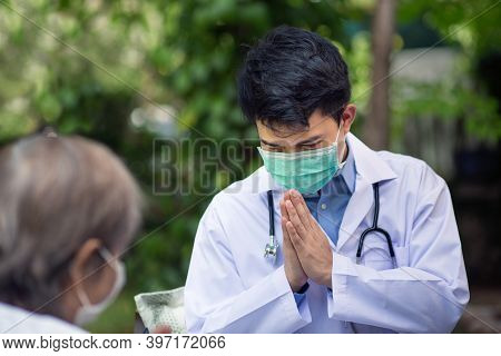 Thai Doctor Greeting (wai) Senior Patient In Wheelchair
