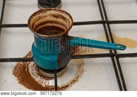Turk Turquoise With Boiled Coffee Standing On A Gas Stove White, It Traces Of Dried Coffee