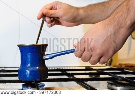 Men's Hands Prepare Coffee In A Blue Enameled Turk On The Gas, Stirring With A Long Teaspoon