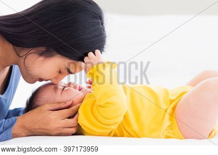 Portrait Of Beautiful Young Asian Mother Kissing Her Infant Newborn Baby In A White Bed, The Mom Lov