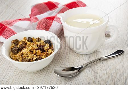Checkered Napkin, White Bowl With Baked Muesli, Pitcher With Yogurt, Teaspoon On Wooden Table