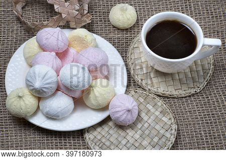 Homemade Meringue Kisses And Coffee Cup. Meringue Cookies On Natural Sackcloth Background.