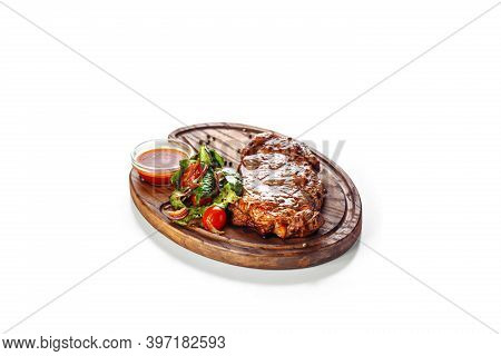 Juicy Appetizing Grilled Steak Served With A Salad Of Tomato And Green Leaves And With Red Sauce. Fo