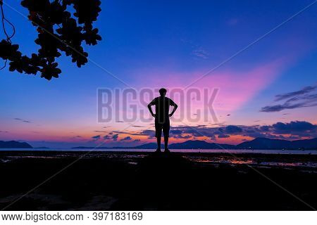 Silhouette Of A Man With Amazing Beautiful Light Of Nature Dramatic Sky Seascape In Sunset Or Sunris