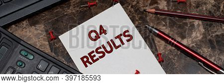 Q4 Results, Text Is Written On A Sheet Of Notepad Lying On A Marble Writing Table Next To A Pen And